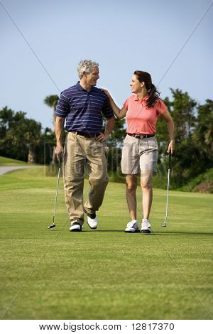 Caucasion mid-adult man and woman walking on golf course talking to each other.