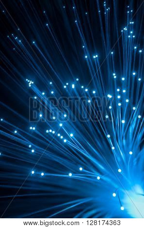 Blue light dots from optic fiber lines over dark background