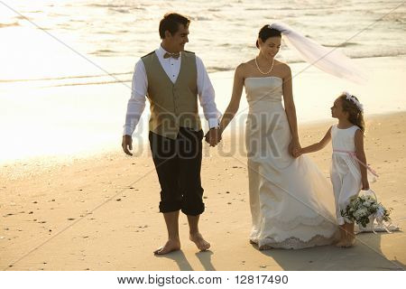 Caucasian mid-adult bride, mid-adult groom and flower girl holding hands walking barefoot on beach.