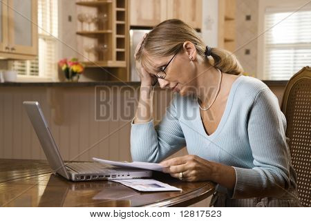 Caucasian mid-adult woman paying bills on laptop computer resting head in hand with worry.