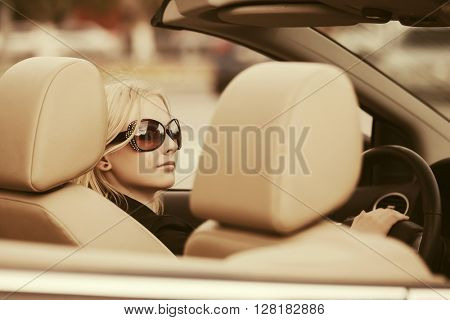 Young woman in sunglasses driving convertible car. Female blond fashion model outdoor