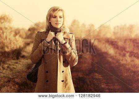 Happy blond fashion woman walking in autumn field. Female blond fashion model with handbag in beige classic coat outdoor