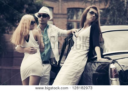 Happy young fashion couple in love next to retro car. Jealous girl. Male and female fashion model outdoor. Young man and woman in sunglasses on city street