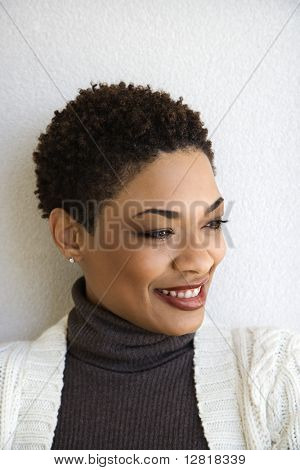 Close up head and shoulder of African-American woman standing against white wall smiling with head turned to side.