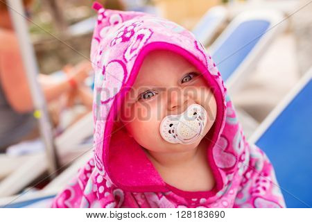 Cute baby girl covered by pink towel at the pool