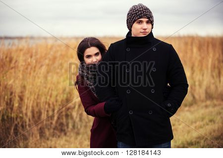 Happy young couple in love walking outdoor. Male and female fashion model outdoor. Young man and woman embracing
