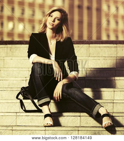 Young fashion business woman sitting on the steps. Female blond fashion model in black jacket outdoor