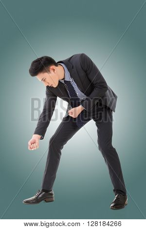 Digging pose or using shovel, full length portrait of Asian young business man.