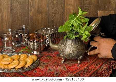 Hands of a muslim woman preparing mint tea the traditional way