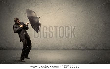 Handsome business man holding umbrella with copy space background concept