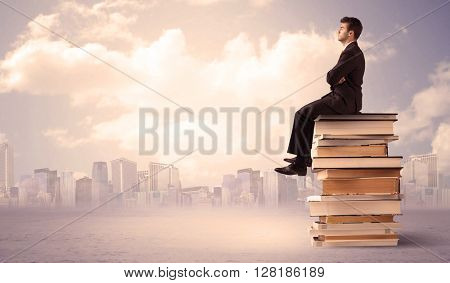 A serious businessman in elegant suit sitting on a stack of books in front of city scape and clouds