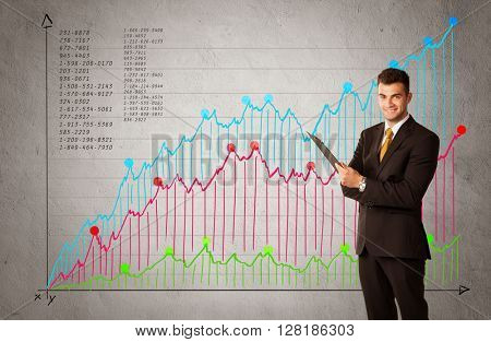 A confident young businessman standing in front of a a chart with graphs and numberswhile talking on the phone concept