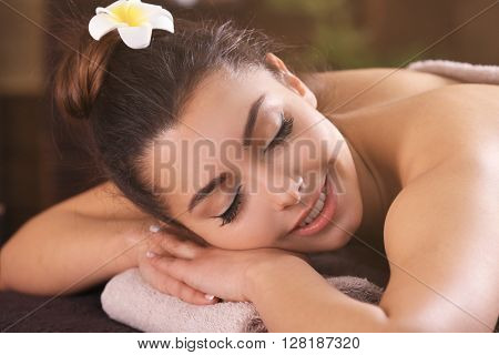 Beautiful young girl with towel lying on massage table in spa salon