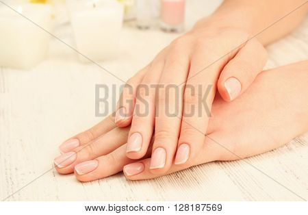 Spa concept. Woman hands with beautiful with pebbles on wooden background, close up