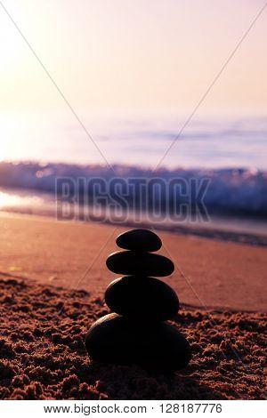 Stones pyramid on the beach at sunset
