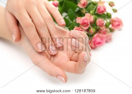 Woman hands with beautiful manicure and roses isolated on white background