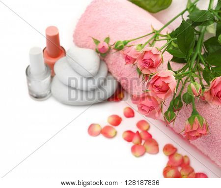 Spa concept. Flower bouquet, towel and pebbles isolated on white background