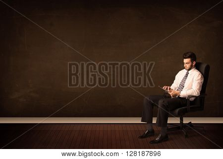 Businessman holding high tech tablet on brown background with copyspace