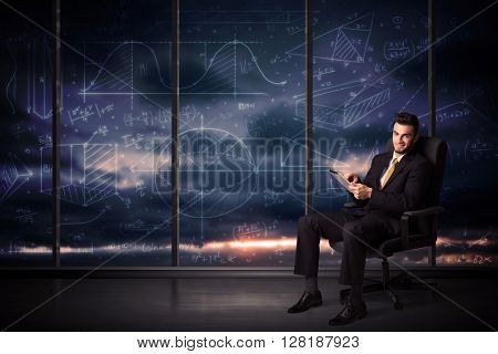 Businessman holding tablet in office room with graph charts on window concept