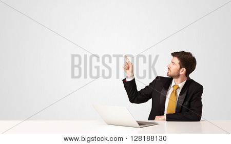 Business man sitting at white table with a white laptop on white background