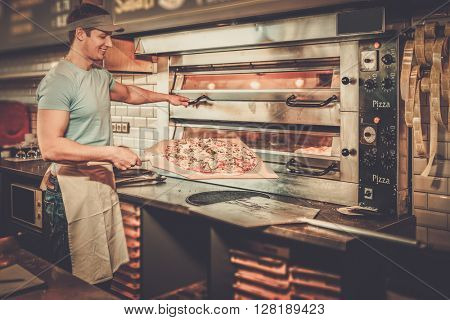 Handsome pizzaiolo making pizza at kitchen in pizzeria.