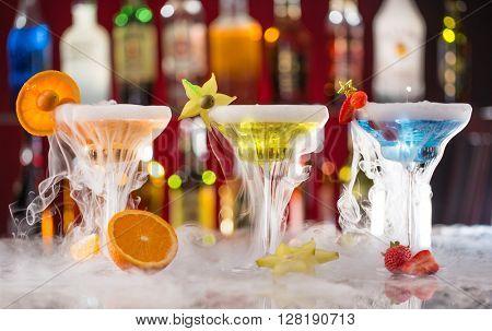 Cocktails with ice vapor on bar desk, close-up.