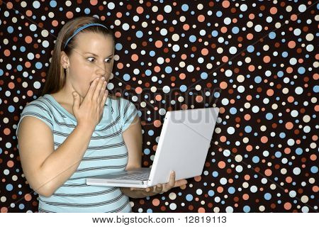 Young Caucasian woman holding laptop looking shocked.