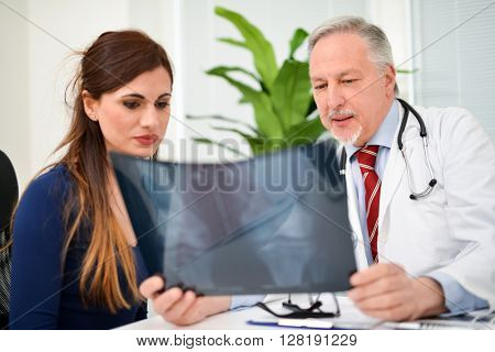 Smiling doctor showing a radiography to his patient