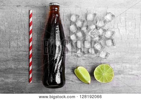 Soda bottle, ice and straw on wooden table