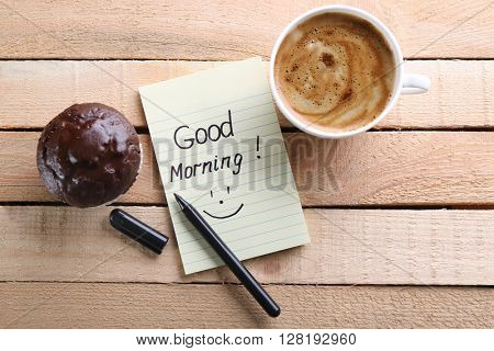 Cup of coffee, chocolate cake and note GOOD MORNING on wooden background