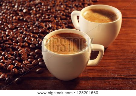 Two cups of fresh coffee with beans on table, closeup