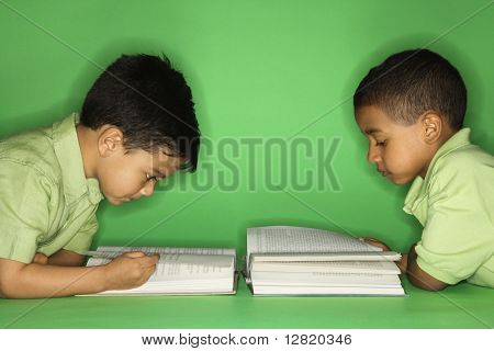Hispanic and African American male child lying reading.