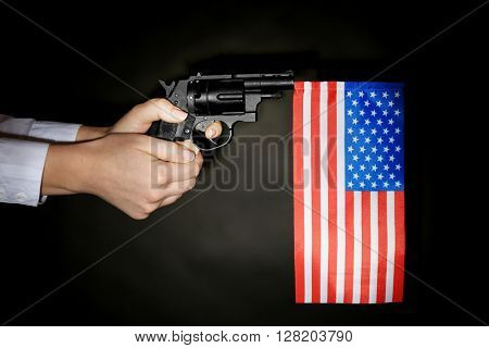 Woman holding handgun with inserted USA national flag on dark lighted background