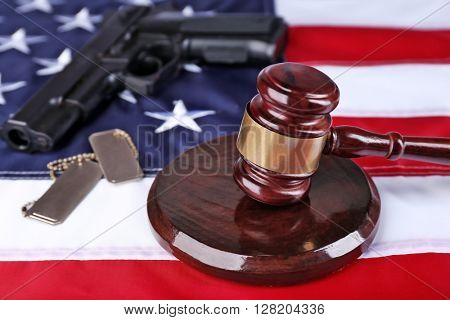 Gavel with gun and tokens on background of USA flag