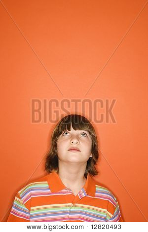 Head and shoulder portrait of Caucasian boy looking up standing against orange background.