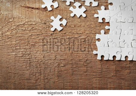 Incomplete puzzles on wooden table