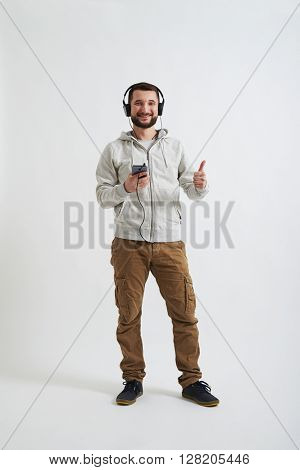 A young bearded man in white hoody and khaki pants is wearing headphones, smiling with his thumb up and holding a phone in his hands