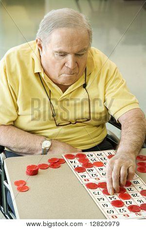 Elderly Caucasian man sitting in wheelchair playing bingo at retirement community center.