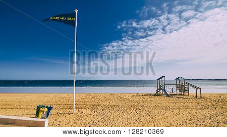 Beach scene empty sandy beach blue sky and children's playground in La Baule France