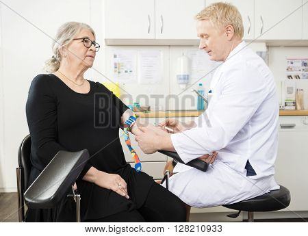 Doctor Collecting Senior Patient's Blood For Test In Clinic