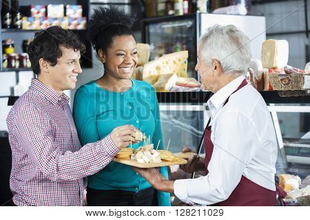 Salesman Offering Cheese Samples To Customers In Shop