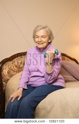 Elderly Caucasian  woman in her bedroom at retirement community center lifting weights to strengthen arms.