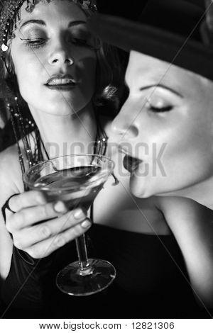 Caucasian prime adult retro female taking drink of girl friend's martini.