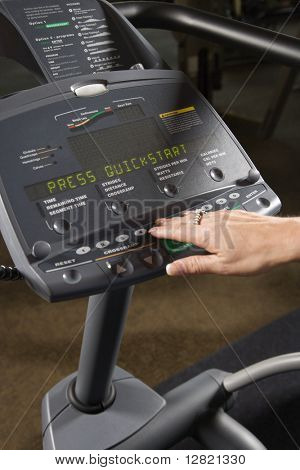 Prime adult Caucasian female setting up elliptical machine at gym.