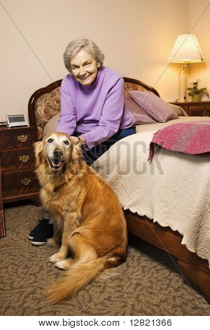 Elderly Caucasian woman and dog in her bedroom at retirement community center.
