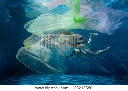The girl floats under water with a cloth.