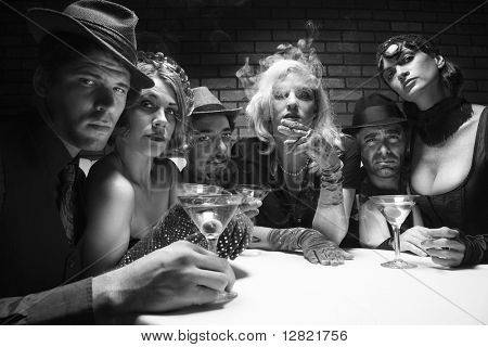 Group of Caucasian prime adult retro males and females sitting at table in lounge looking at viewer.