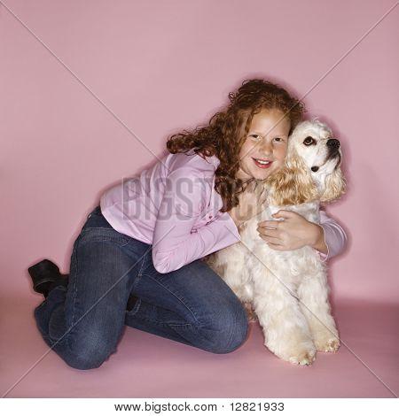 Caucasian female child hugging Cocker Spaniel dog.