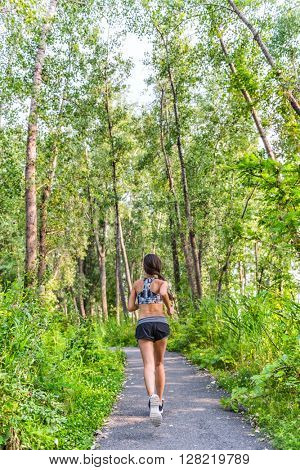 Runner woman training cardio running on forest path in city park in summer nature. Back of girl jogging living a healthy active lifestyle wearing sports activewear clothing working out full length.