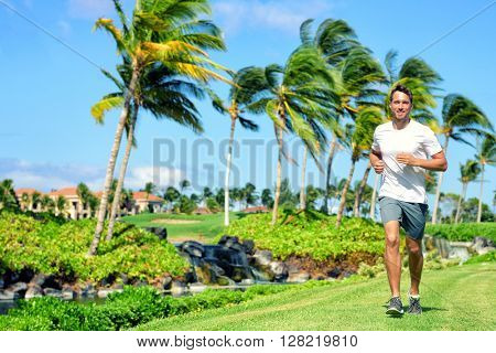 Active lifestyle man runner jogging in high end luxury residential american tropical neighborhood - Miami Florida living. Healthy running male fitness athlete working out cardio on grass in summer.